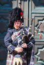 A scotsman wearing traditional scottish outfit playing the bagpipes edinburgh scotland may along royal mile in edinburgh on th Royalty Free Stock Photo