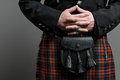 Scottish kilt and purse a man s hand clasped over a Royalty Free Stock Photo