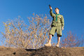 Scout standing on a rock taking a compass reading Royalty Free Stock Photo