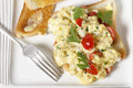Scrambled egg and tomatoes from above on toast with cherry parsley pepper cooking in a bain marie allows the to be incorporated Royalty Free Stock Photography