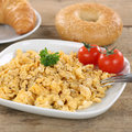 Scrambled eggs for breakfast on a plate with bagels and croissant Royalty Free Stock Photography