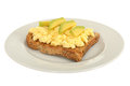 Scrambled eggs breakfast on wholemeal toast with avocado a plate isolated white background Royalty Free Stock Images