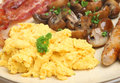 Scrambled eggs cooked english breakfast with bacon sausages and sauteed mushrooms Royalty Free Stock Image