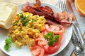 Scrambled eggs with fresh tomatoes and fried bacon breakfast chive Royalty Free Stock Photo