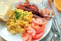 Scrambled eggs with fresh tomatoes and fried bacon breakfast sliced orange Stock Image