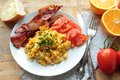 Scrambled eggs with fried bacon breakfast and fresh tomatoes Stock Photos