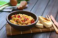 Scrambled eggs with red bell pepper made and green onion in rustic bowl toasted bread on the side photographed natural Stock Photo