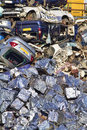 Scrapyard cars crushed into cubes in foreground with those awaiting compaction in the background Stock Image