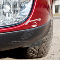 Scratch on a car s bumper right under the headlight Royalty Free Stock Photo
