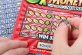 Scratch ticket a human hand is scratching a lottery Royalty Free Stock Photo