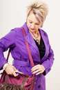 Scratching in my bag a caucasian woman dressed a vibrant purple trench coat digging her leather handbag resting over her shoulder Royalty Free Stock Images