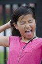 Scream young asian girl screaming as she pulls her hair Stock Photo