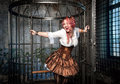 Screaming beautiful steampunk woman in the cage with pink hair sitting metal Stock Photography