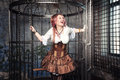 Screaming beautiful steampunk woman in the cage with pink hair sitting metal Royalty Free Stock Photos