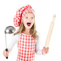 Screaming little girl in chef hat with ladle and  rolling pin Royalty Free Stock Photo