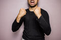 Screaming man with fists raised young in a black top is raising his and Royalty Free Stock Image