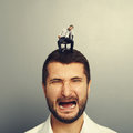 Screaming man with small bored man portrait of sad on the head Stock Photo
