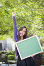 Screaming mixed race female student holding blank chalkboard portrait of an attractive excited and carrying backpack on school Stock Photo