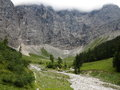 Scree slopes in massive mountains landslips down high mountain into a secluded green valley alpine park karwendel austria Stock Photo