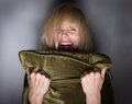 Screeming moment of fear mentally ill woman hiding in screaming behind pillow Stock Photos