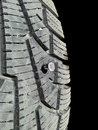 Screw in tire into rubber isolated towards black background Royalty Free Stock Photography