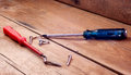 Screwdriver blue and red on a wooden table. Royalty Free Stock Photo
