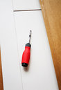 Screwdriver on a board in the process of setting up recently purchased furniture tilt shift lens intentionally used for better Stock Photos