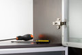 Screwdriver and concealed hinge an adjustable fixed on a modern cabinet with a glass door two screwdrivers Royalty Free Stock Images