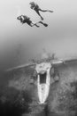 Scuba divers ascend from the wreck of an underwater aircraft above airplane Royalty Free Stock Photography