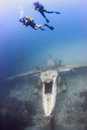 Scuba divers ascend from the wreck of an underwater aircraft above airplane Stock Photo