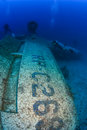 Scuba divers explore the wreck of an aircraft wing underwater airplane Stock Photo