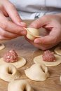 Sculpt dumplings with minced meat close up vertical cook hands Stock Image