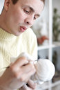 Sculptor carefully works on plaster statuette Royalty Free Stock Photos