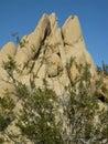 Sculptural granite rock formation with triangular peaks set against a blue Mojave Desert sky