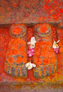 Sculpture of feet symbolising deity in hinduism pair sculptured covered with red substances and flowers hindu temple Royalty Free Stock Photo