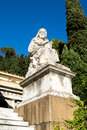 Sculpture of a mighty god make marble stone sitting and looking forward with blue sky and green trees Stock Photography
