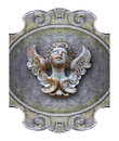 Sculpture of a wooden angel against an old classical plaster Royalty Free Stock Photo