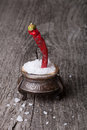 Sea ​​salt in a large antique salt shaker and hot red pepper on old wooden table Stock Image