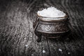 Sea salt in a large antique salt shaker on old wooden tabl Royalty Free Stock Photo