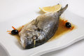 Sea ​​bream dorada with lemon in the sauce on the plate Royalty Free Stock Photography