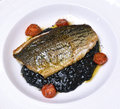 Sea bass black sea bass served black risotto Royalty Free Stock Image