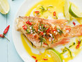 Sea bass steamed with chili pepper rosemary bacon and shallot onion in olive and linseed oil shallow dof Royalty Free Stock Photo