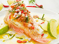 Sea bass steamed with chili pepper rosemary bacon and shallot onion in olive and linseed oil shallow dof Stock Photography