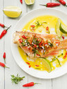 Sea bass steamed with chili pepper rosemary bacon and shallot onion in olive and linseed oil shallow dof Stock Photos