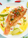 Sea bass steamed with chili pepper rosemary bacon and shallot onion in olive and linseed oil shallow dof Royalty Free Stock Photos
