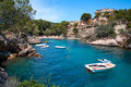 Sea bay a beautiful summer day blue clear water and granite stones. Boats above coral reef. Spain. Royalty Free Stock Photo