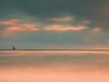 Sea birds  on boulder sticking out from smooth wavy sea. Evening wavy ocean. Dark horizon with the last sun rays. Soft focus Royalty Free Stock Photo