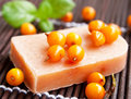Sea buckthorn natural soap with raw berries and green leaves on bamboo board Royalty Free Stock Images