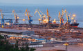 Sea commercial port at night in Mariupol, Ukraine. Industrial view. Cargo freight ship with working cranes bridge in sea port at t Royalty Free Stock Photo