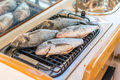 Sea fish is grilled on a grill while sailing Royalty Free Stock Photo